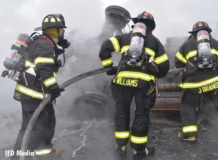 Three firefighters with hoseline at tanker fire