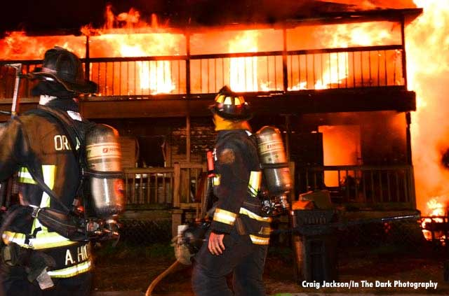 Firefighter with SCBA surveys the scene of a massive house fire