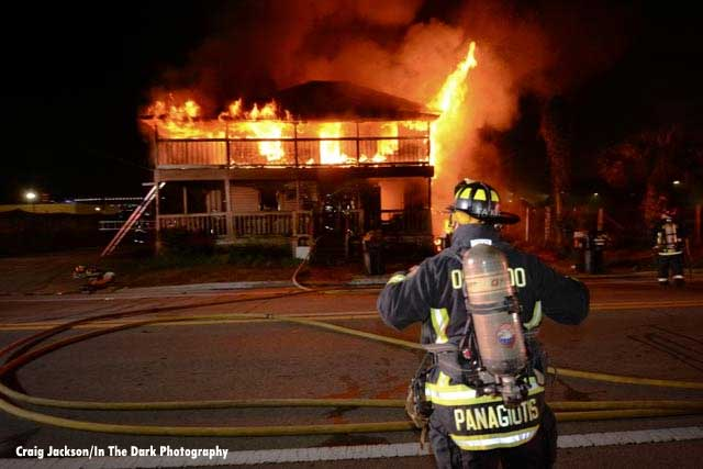 A firefighter wearing SCBA with hoselines and a home in fire behind him
