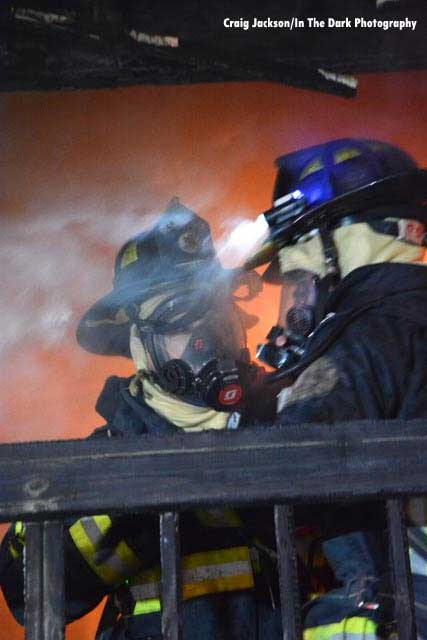 Firefighters in SCBA with flames in the background