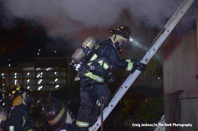 A firefighter in full gear on a ladder on the fireground