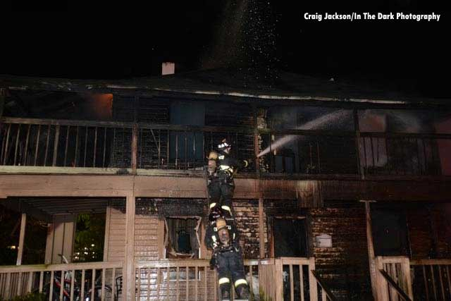 Firefighters administer a hose stream on the blackened exterior of a home