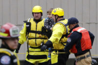Firefighters with a rescued child after evacuations in Washington state