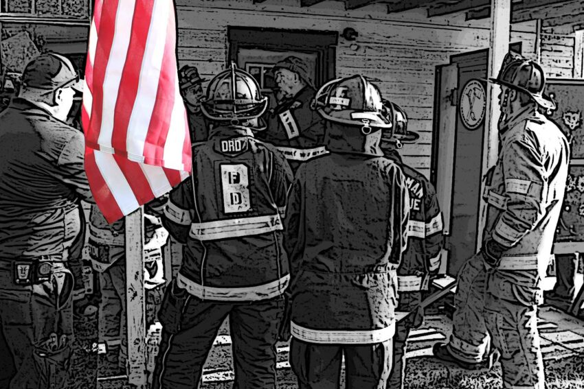 Firefighters stand on a porch with an American flag
