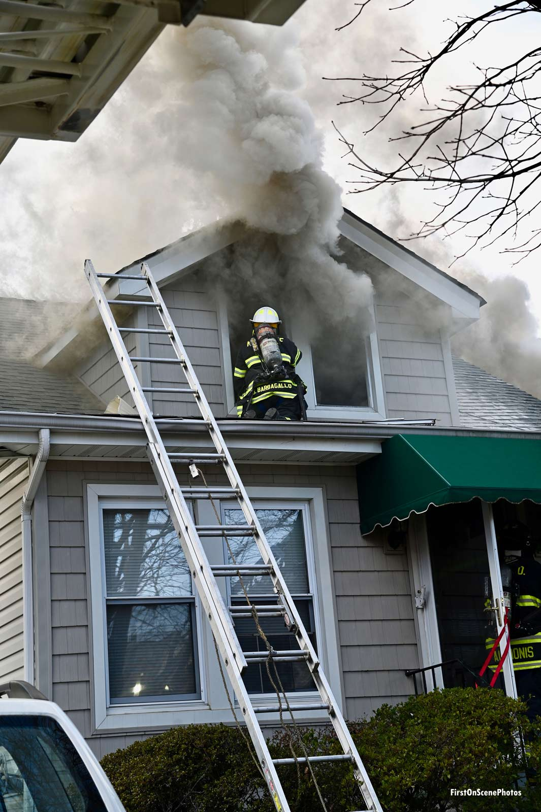 A firefighter on the exterior of a roof while smoke shoots from an upper floor