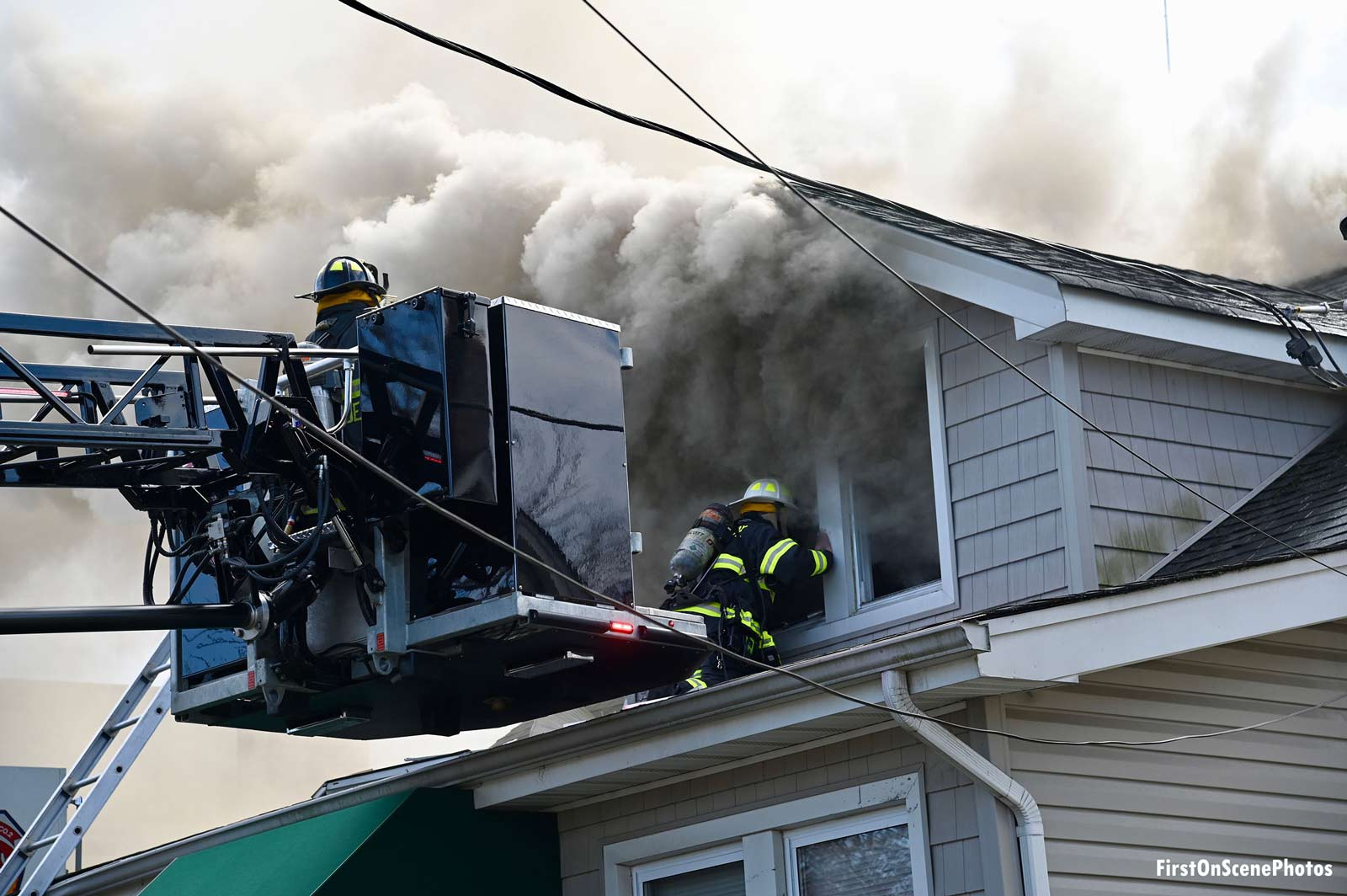 Smoke shoots from the windows as firefighters work in the bucket and on a roof at a house fire