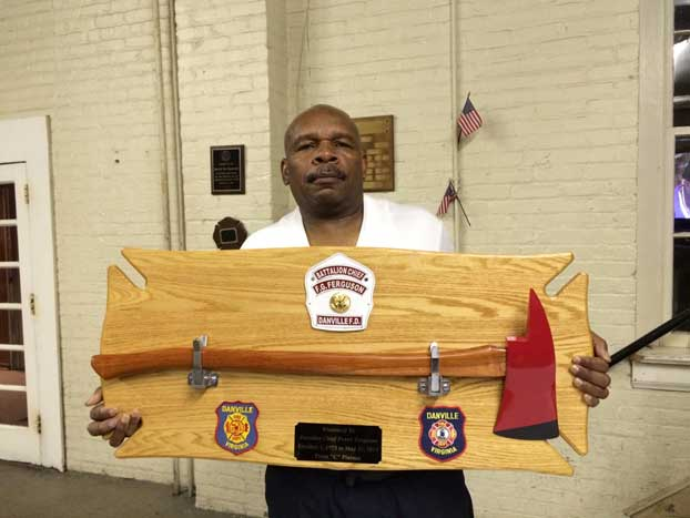 Battalion Chief Frank Ferguson holding his fire ax plaque that was presented by his shift on his last working day.