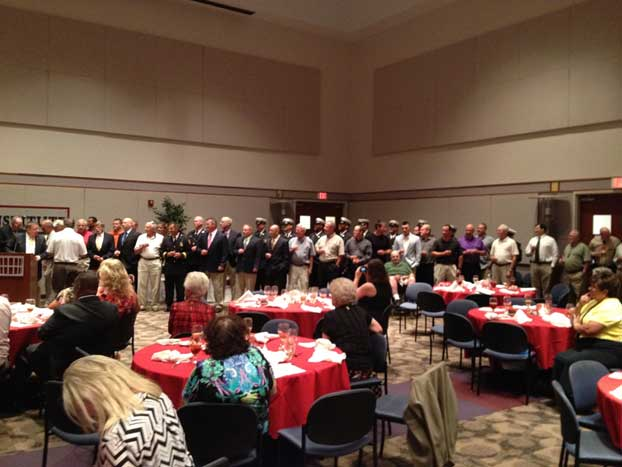 Active and retired firefighters gather at the front of the room to pose a toast for the new retirees.