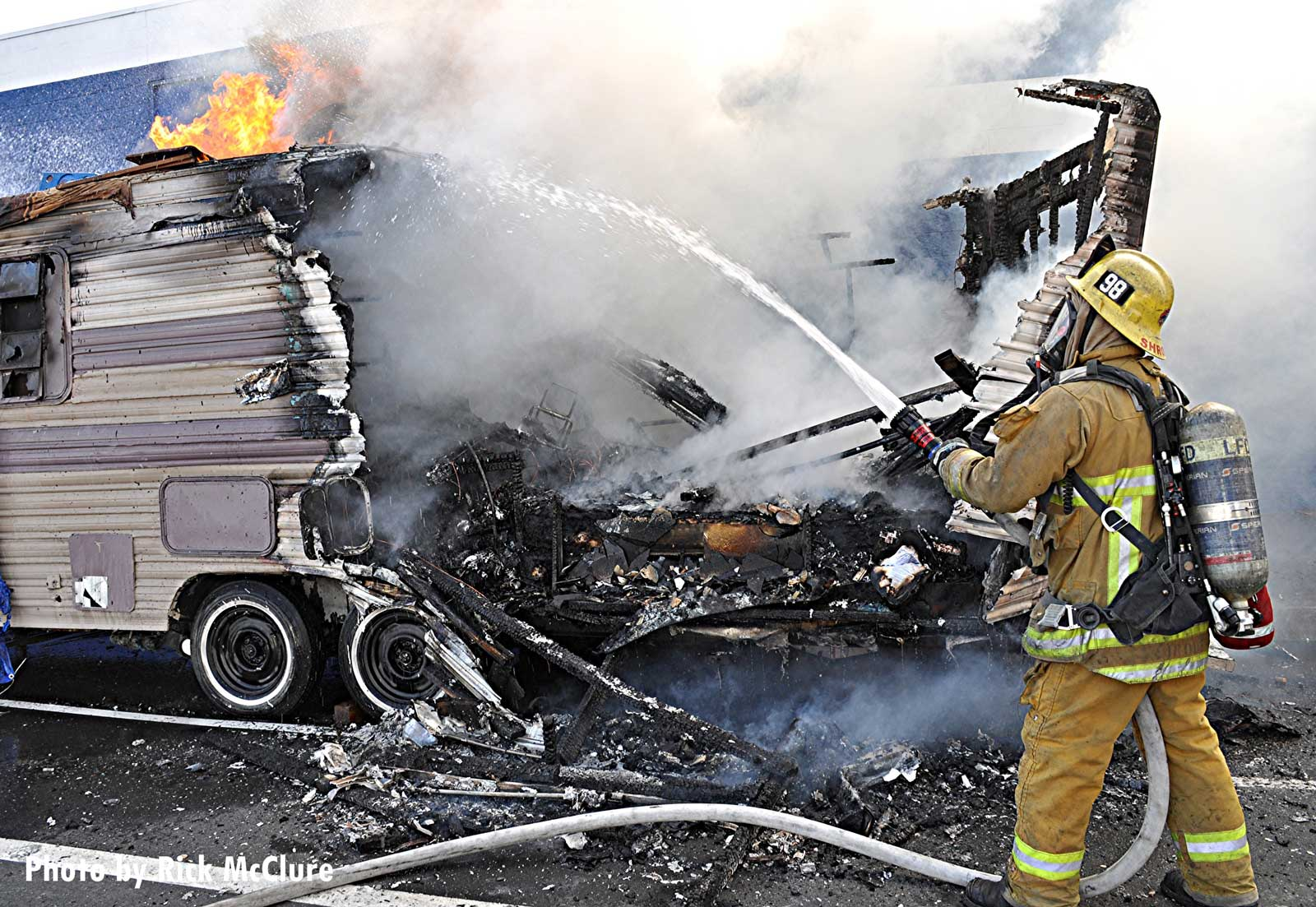 Firefighter sprays water on a burning trailer