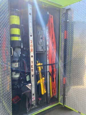 Various firefighter tools including a ladder stored inside a fire truck compartment