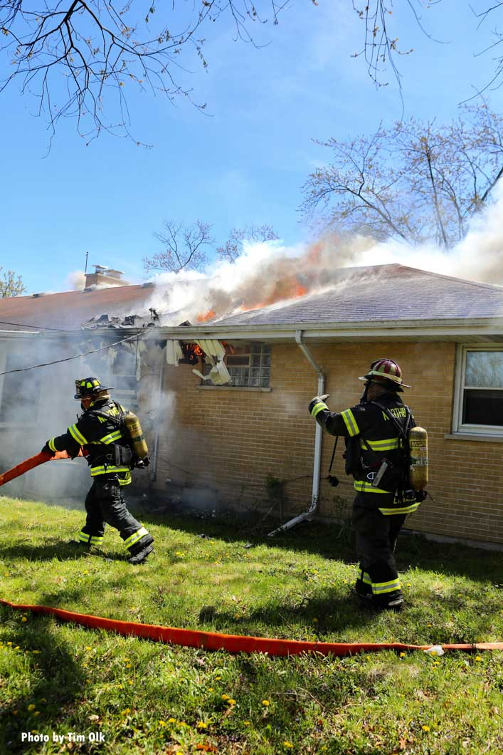 Firefighters moving hoselines as flames vent from the house fire