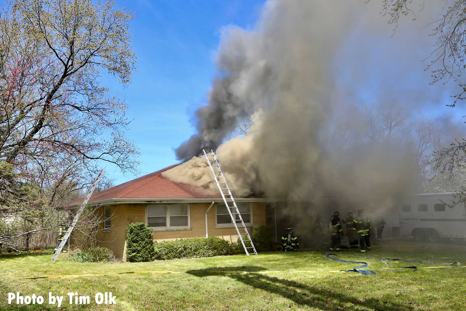 A ladder up to the roof of the vacant home with smoke showing