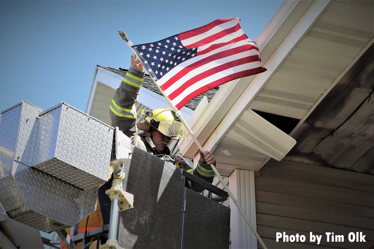 A firefighter retrieves an American flag from the scene of a major apartment fire in East Troy