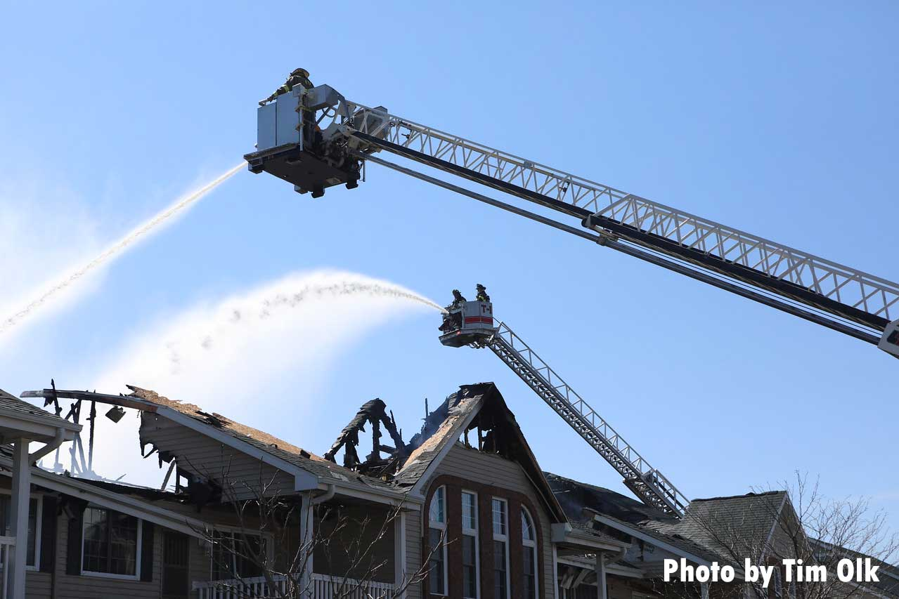 Tower ladder buckets with elevated master streams pour water on the fire