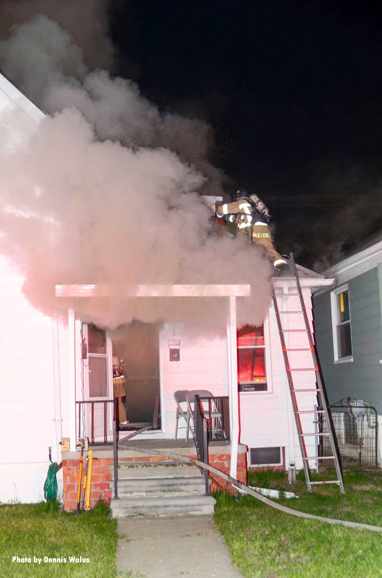 A firefighter climbs a ladder and makes it on to the roof amidst smoke