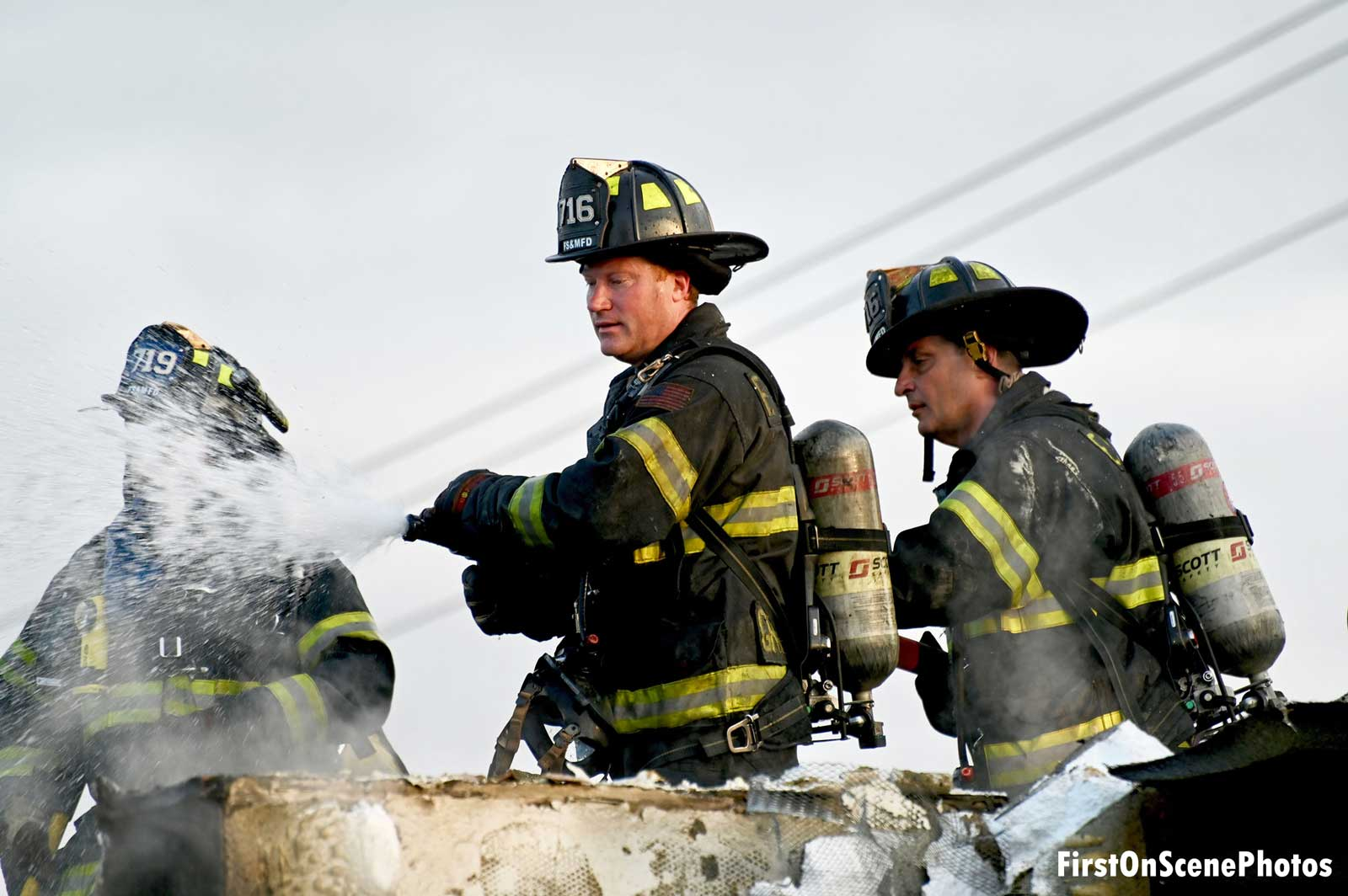 Firefighters maneuver a hose stream