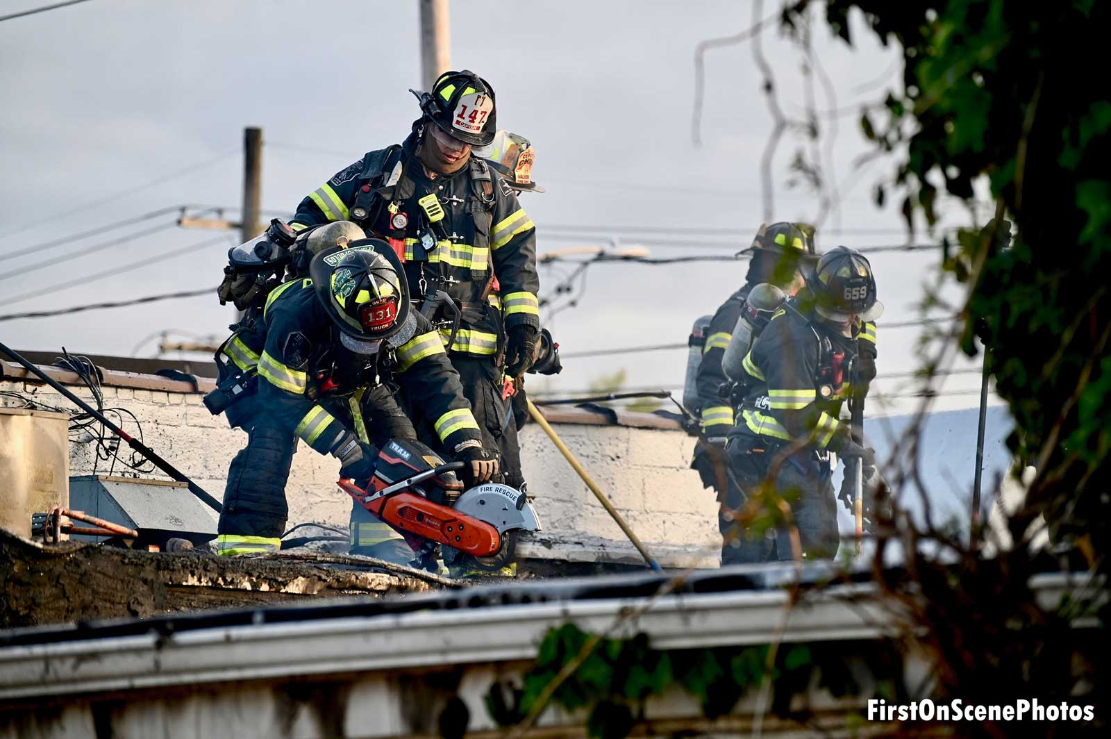 Multiple firefighters work the roof of a structure