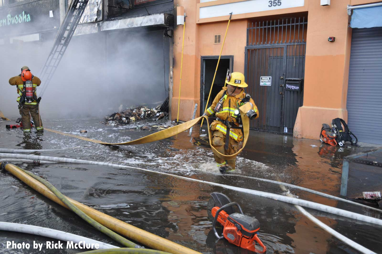 A firefighter moving hose at the explosion