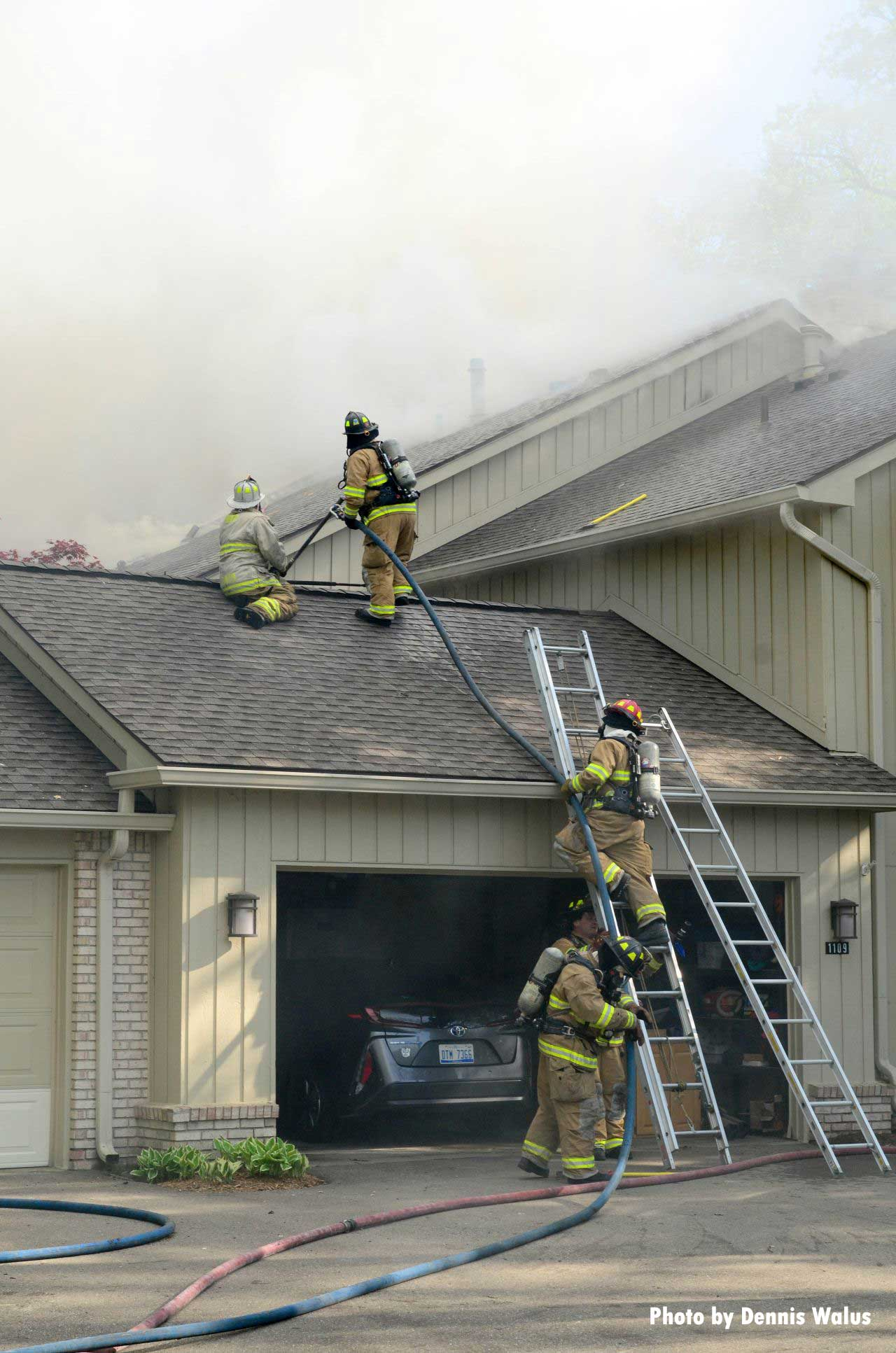 Firefighters stretch a line onto the roof of the building