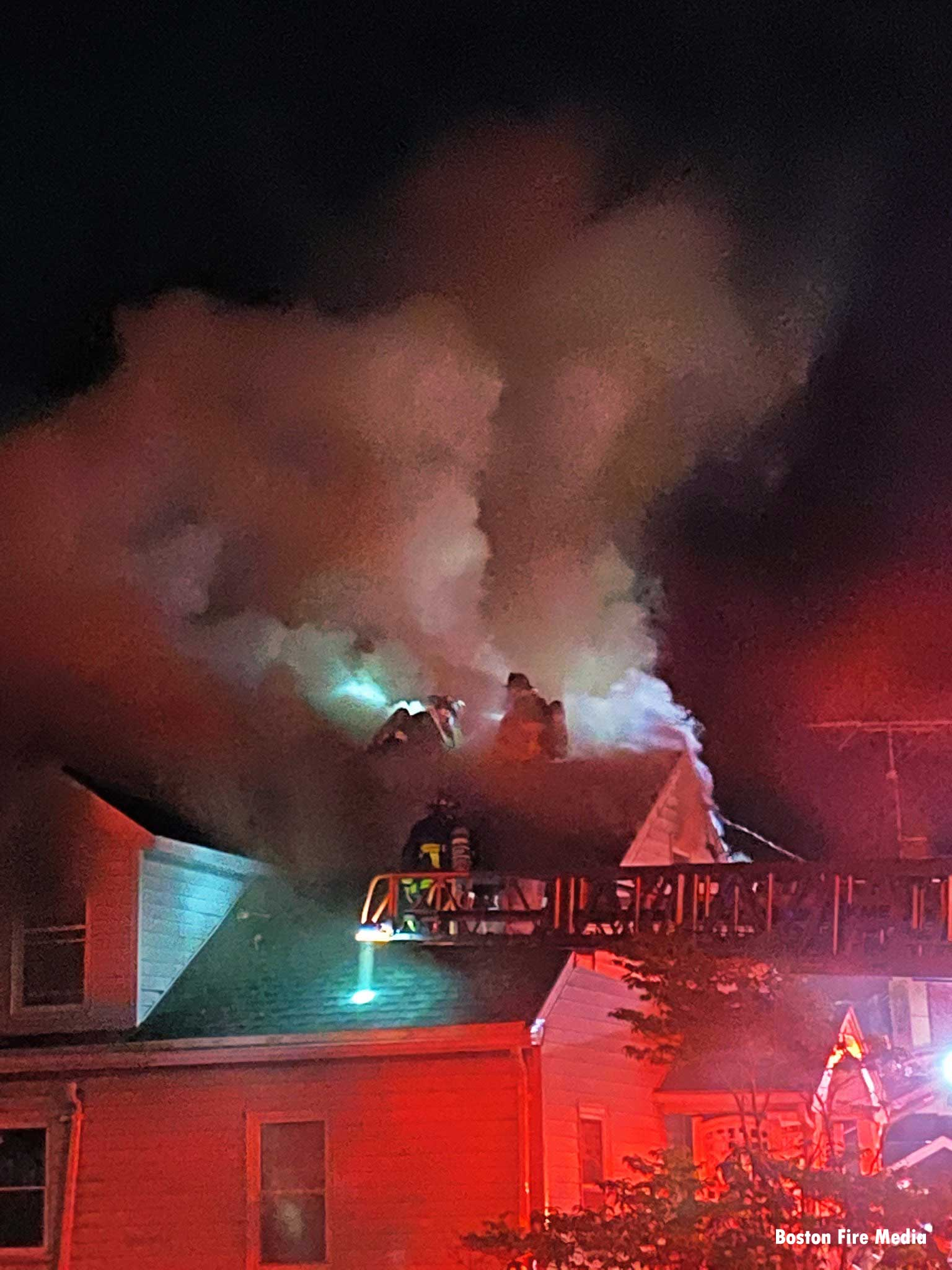 Aerial ladder and Boston firefighters on roof