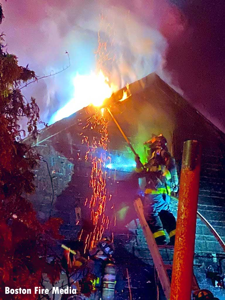 Boston firefighter on a ladder as flames vent from roof