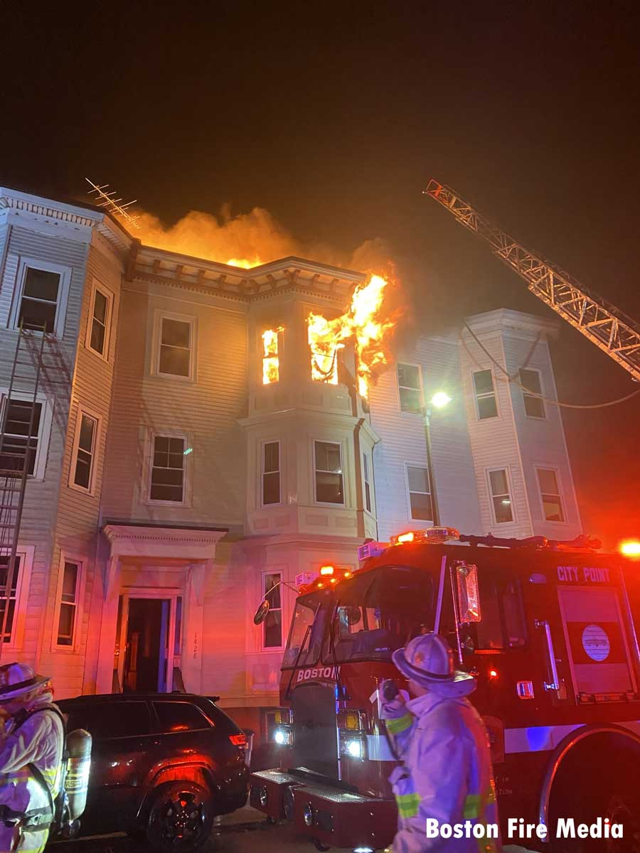 An elevated stream as fire shoots from the top of a building in South Boston