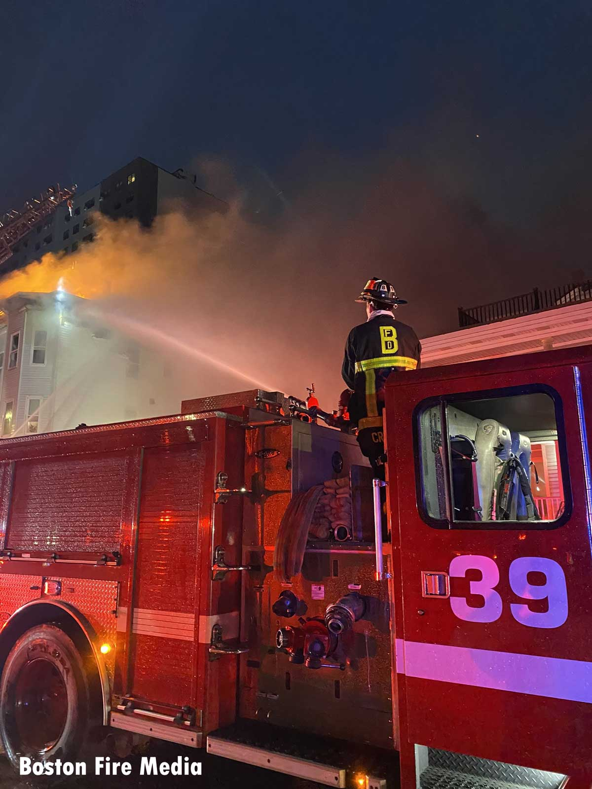 Boston fire apparatus with firefighter using master stream