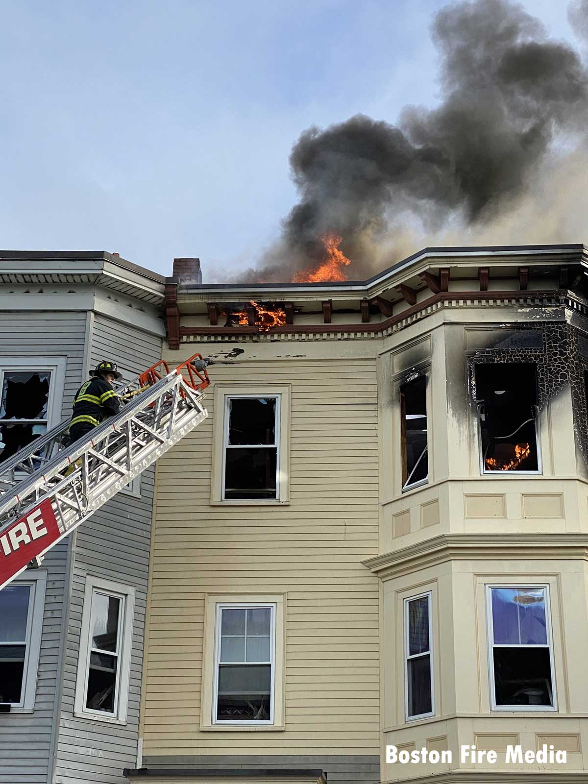 Firefighter in a an aerial continues to battle hot spots hours after the fire