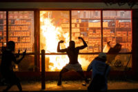 Man poses in front of burning store