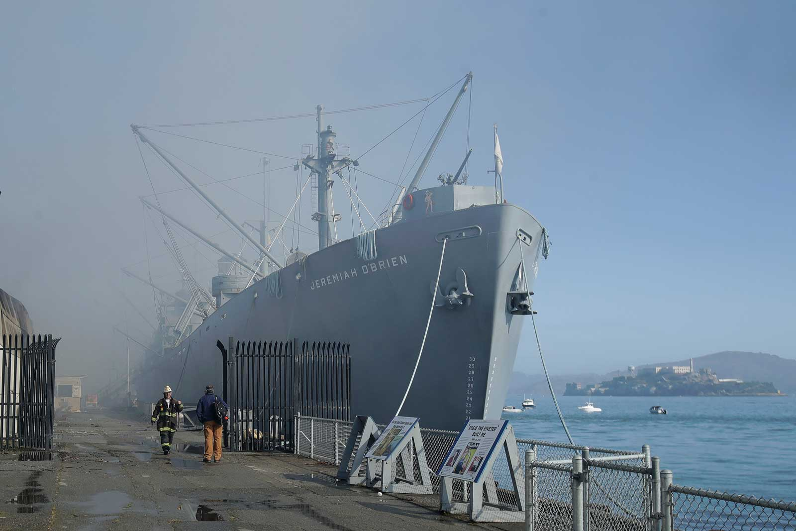 Fire officials stand in front of the SS Jeremiah O'Brien ship after a fire broke out