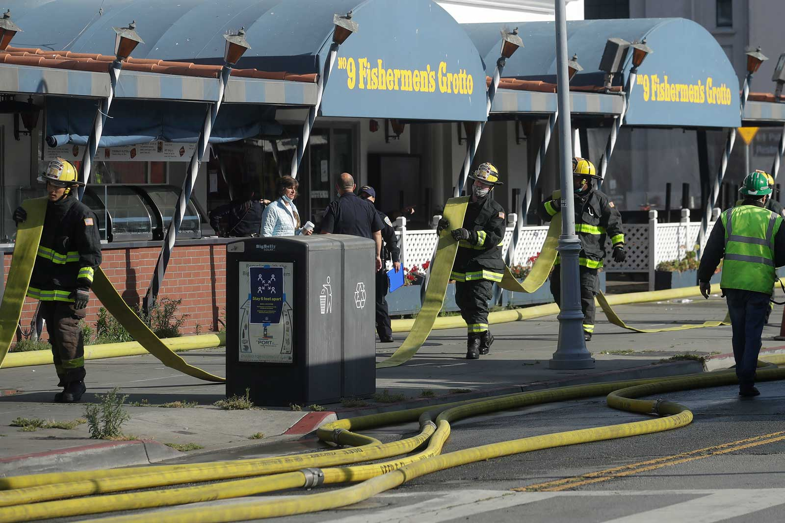Firefighters carrying hose