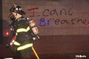 Firefighter with I Can't Breath graffiti on wall