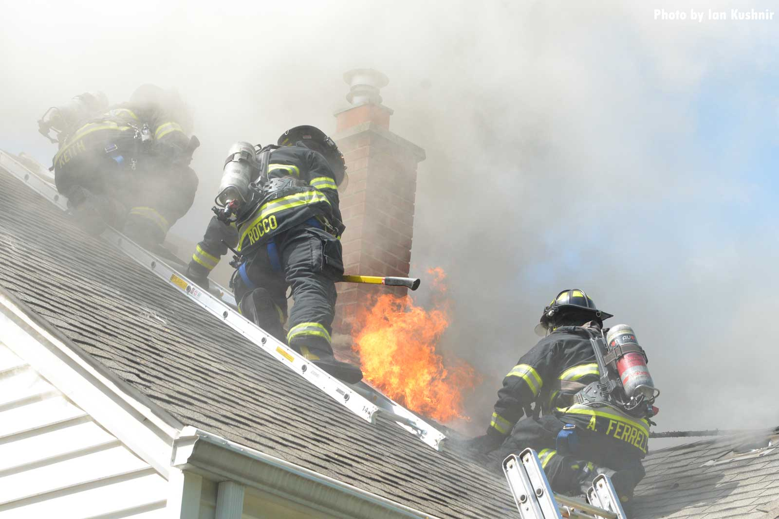 Firefighters move as flames erupt from the roof