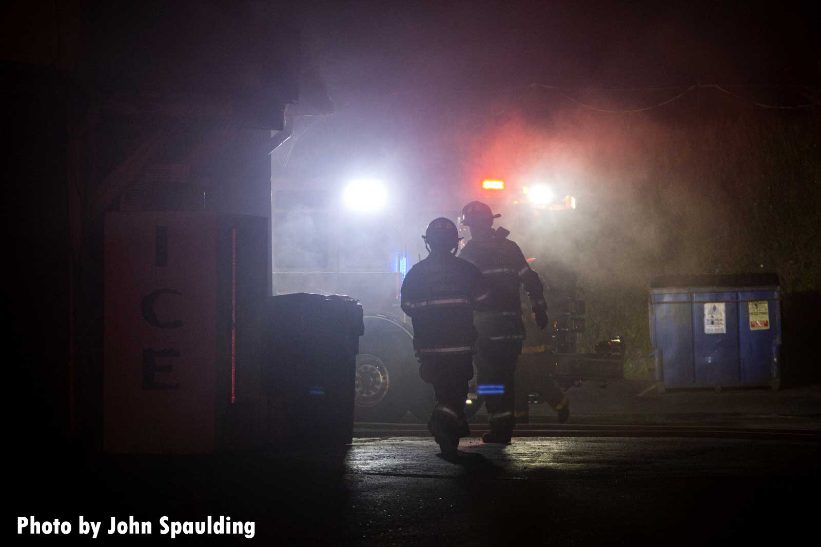 Firefighters navigating through the haze of the fire scene