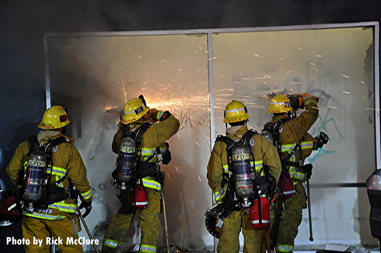 Los Angeles firefighters using saws to force entry