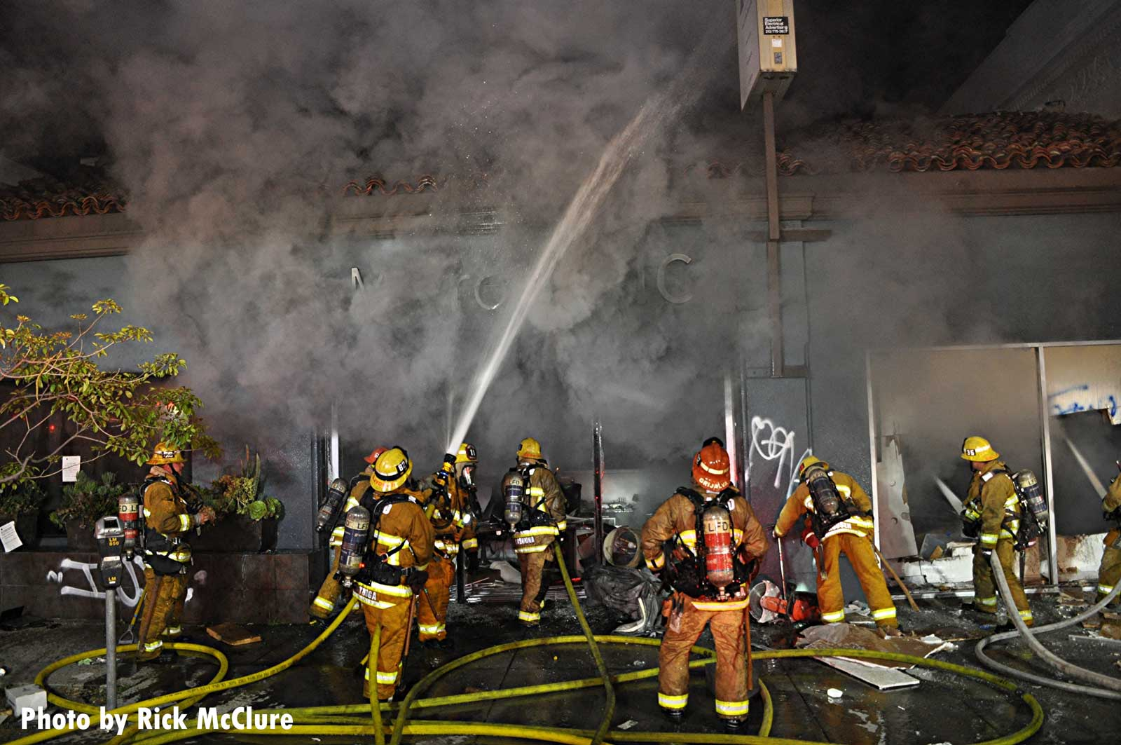 LAFD firefighter manages a hoseline as smoke covers the scene