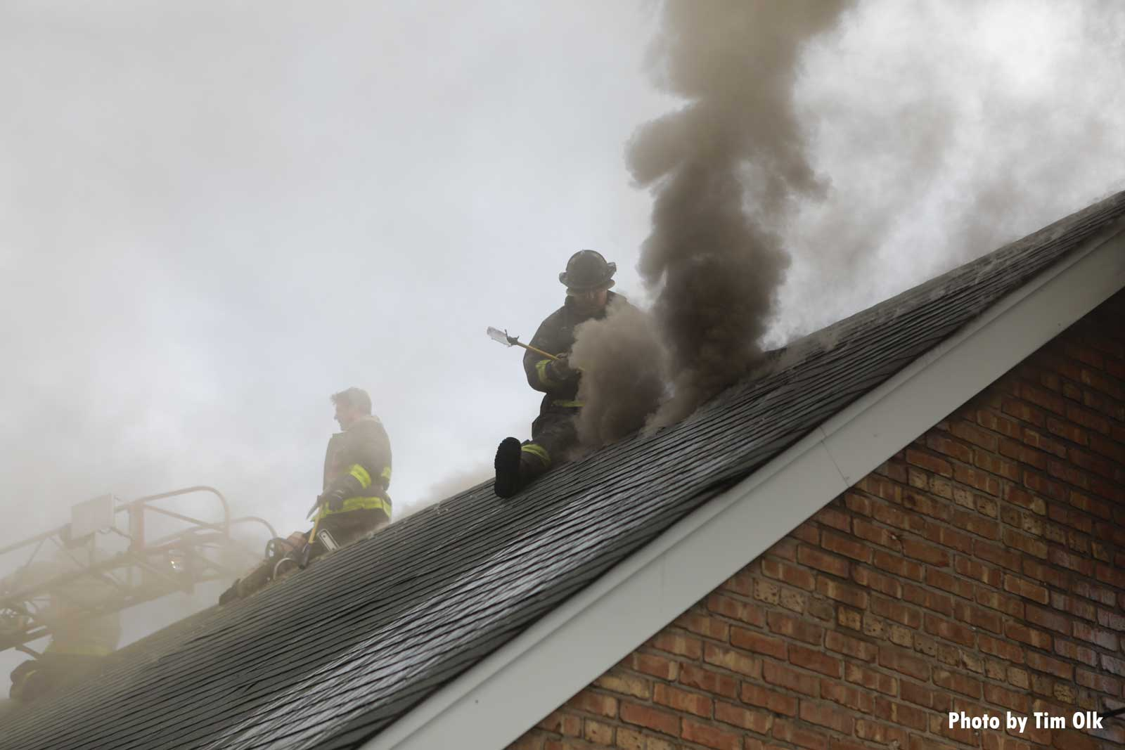 Chicago firefighter on the roof of a burning home with smoke
