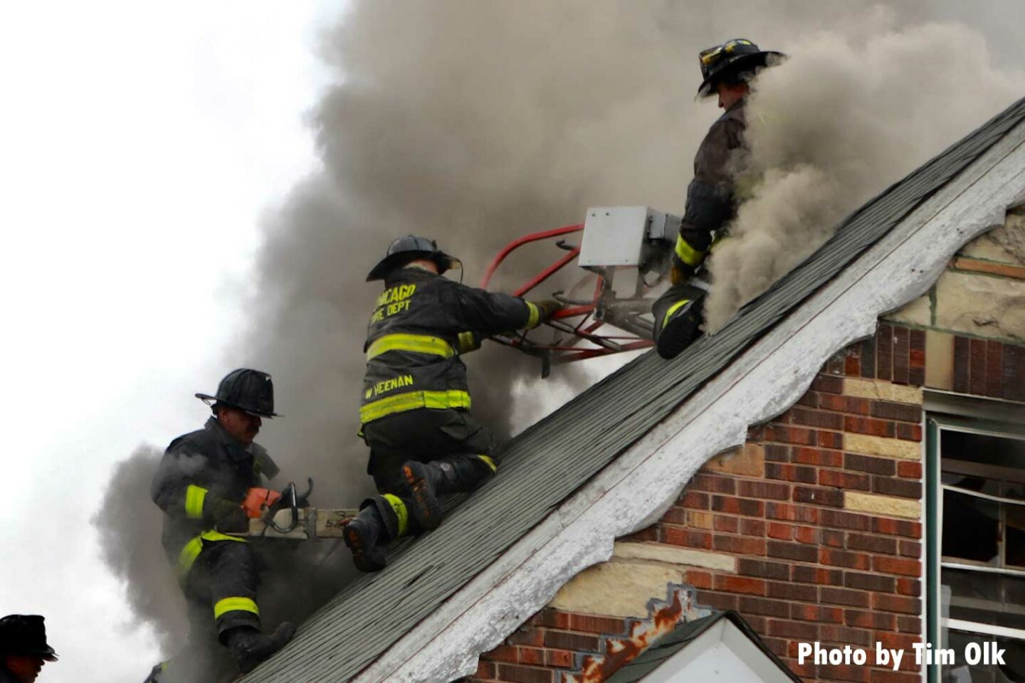Firefighter with a power saw operating on the roof of a home