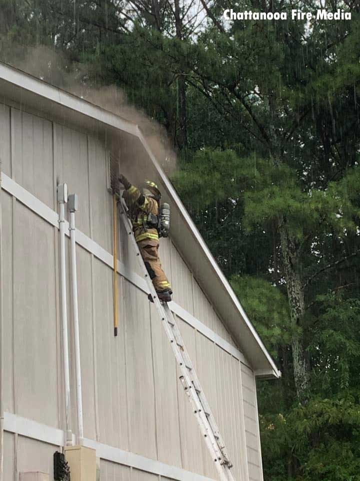 A firefighter on a ladder at a window filled with smoke