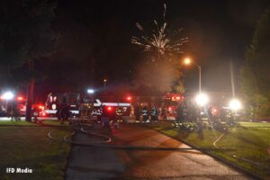 Fireworks exploding over a fire apparatus