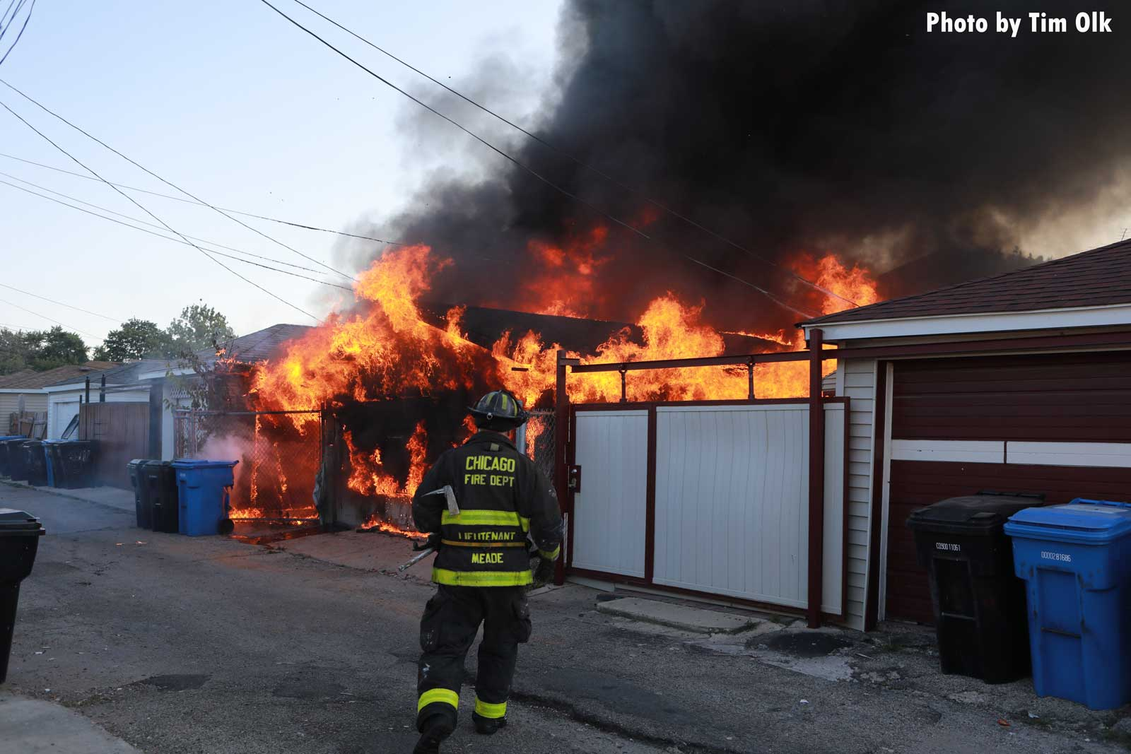 Massive flames rage from the garage with a Chicago firefighter