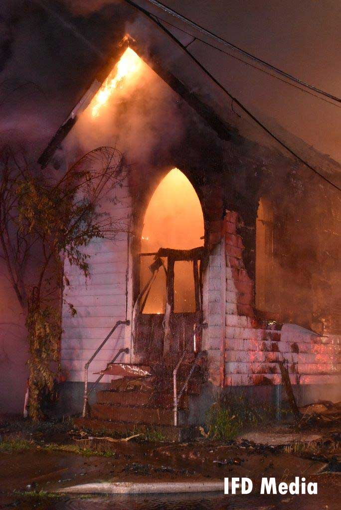 Flames cast an eerie light through the front of the church