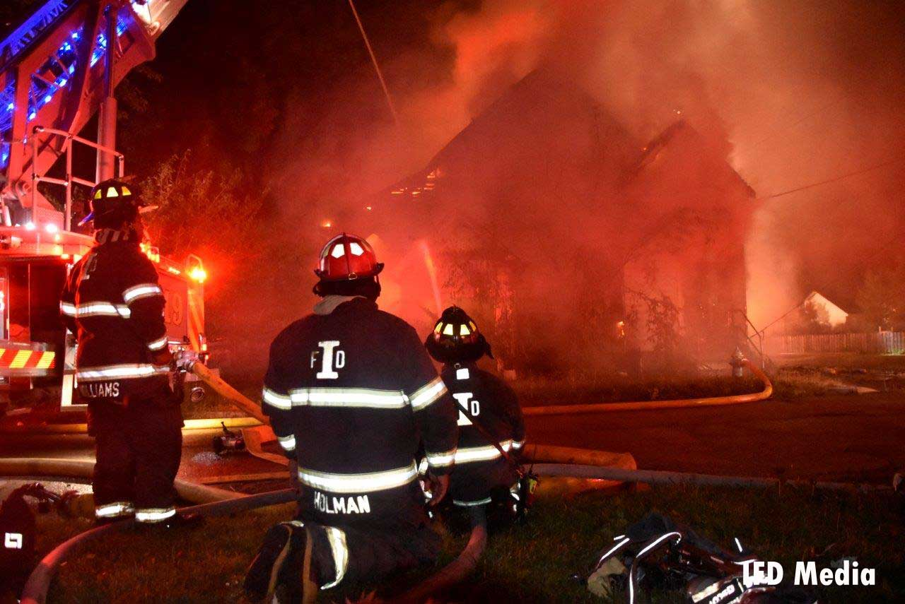 Indianapolis firefighters in front of a burning church building