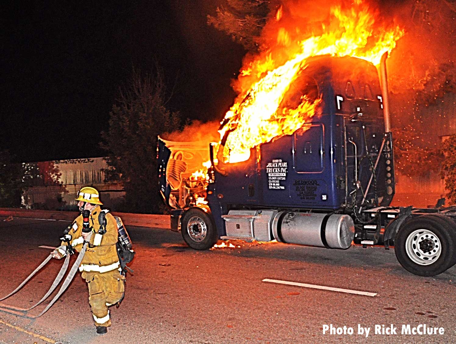 A firefighter stretches a hoseline in front of a burning tractor trailer