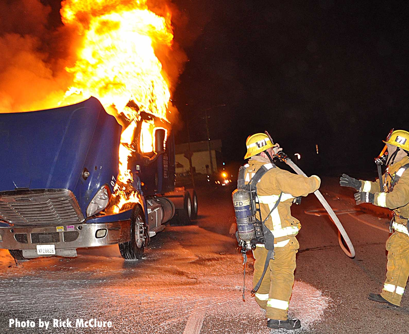 Two firefighters with a hoseline at a big rig fire