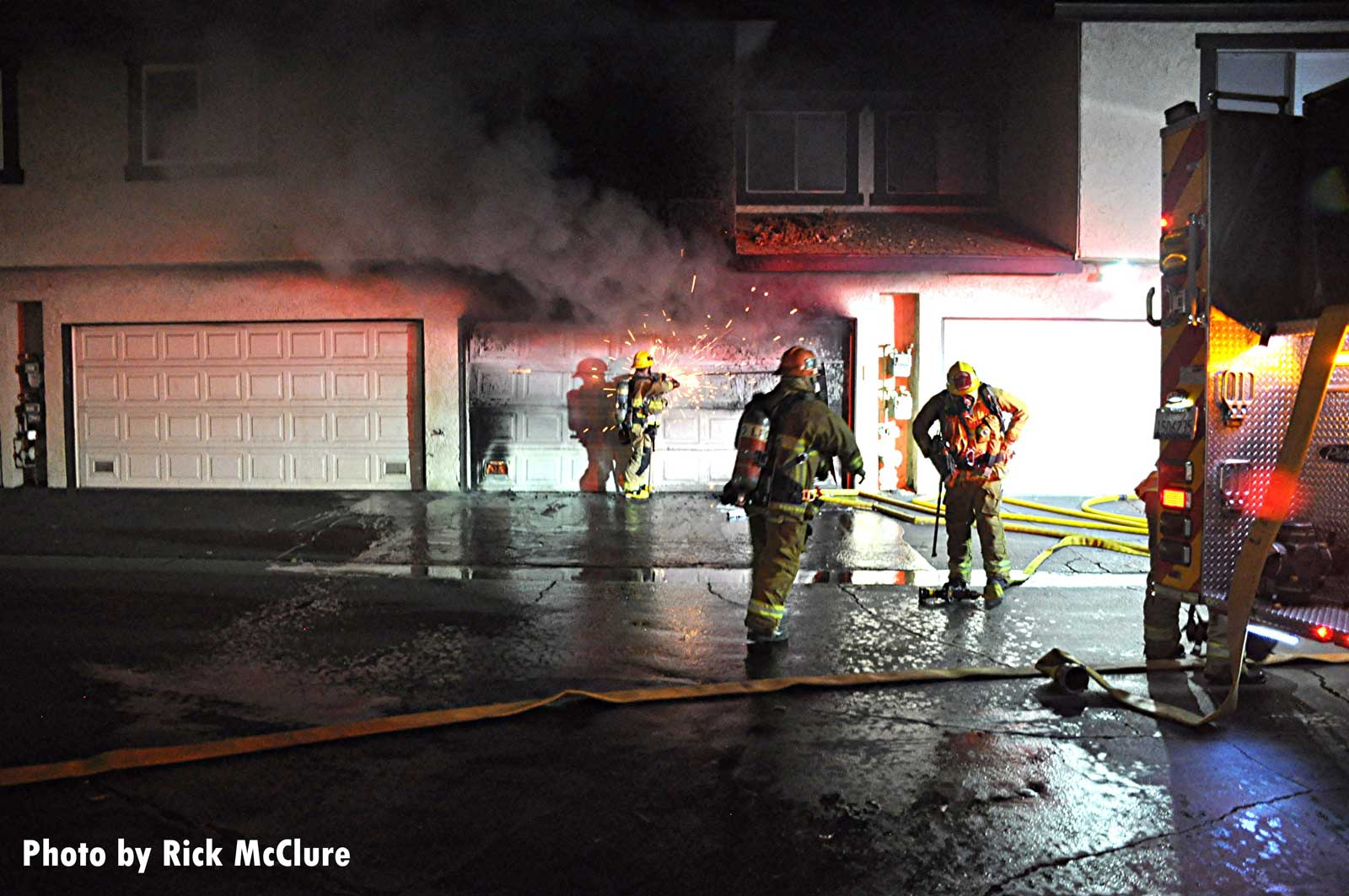Firefighters work to gain access to a garage