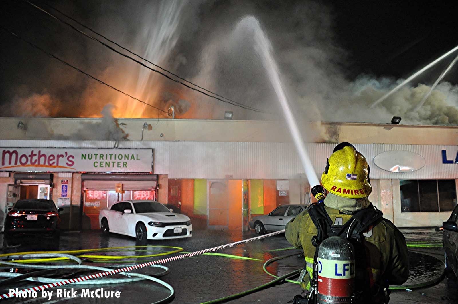 A City of Los Angeles firefighter with a hose putting water on the flames shooting from a building
