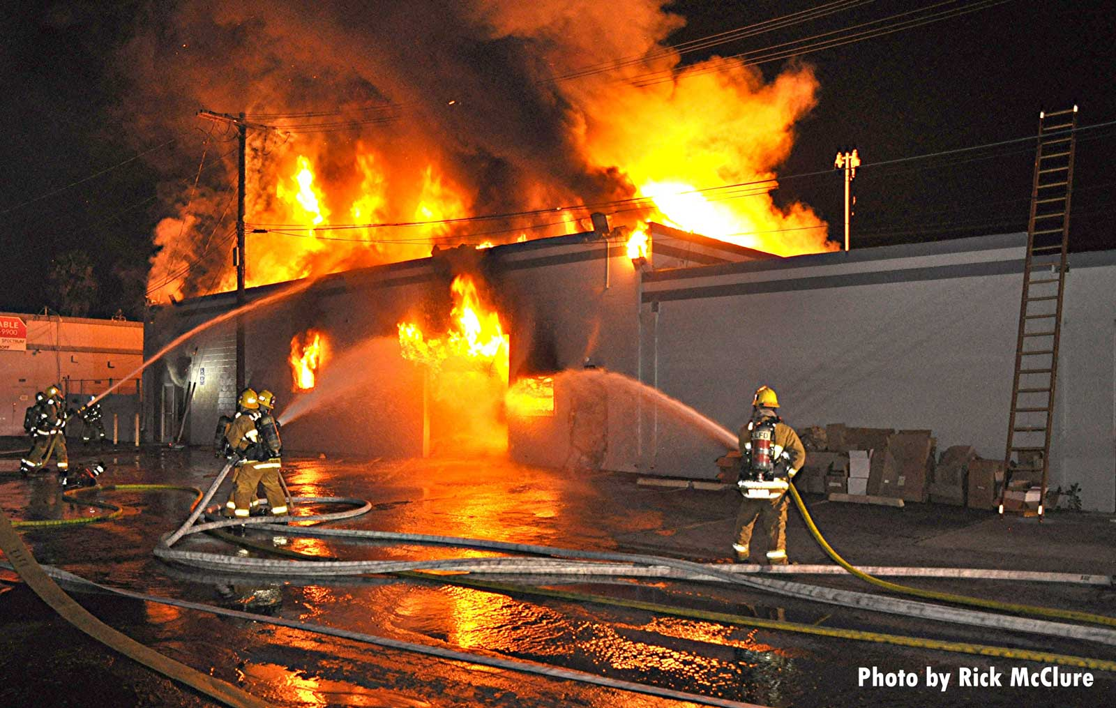 Firefighters train hoselines on a burning building in Los Angeles