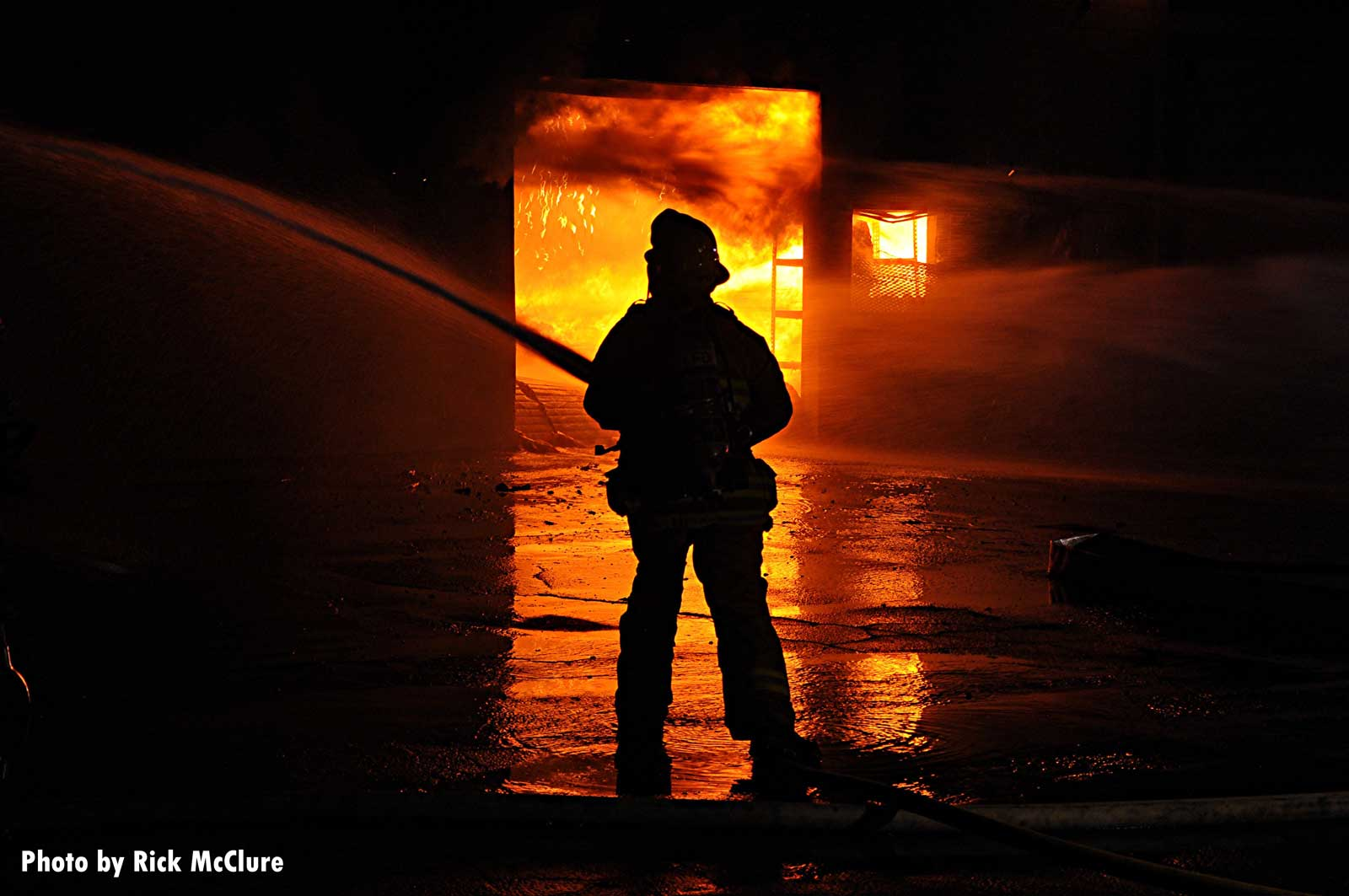 Firefighter with a hoseline framed by flames