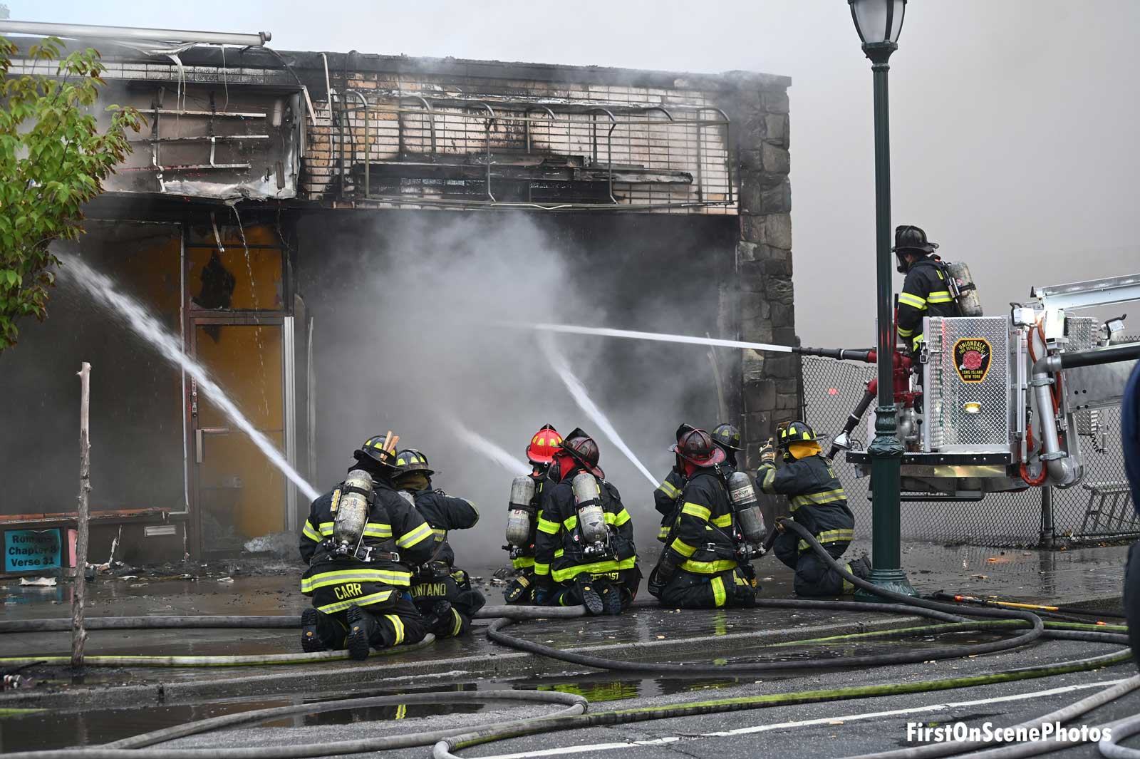 Firefighters use multiple handlines on exterior of businesses
